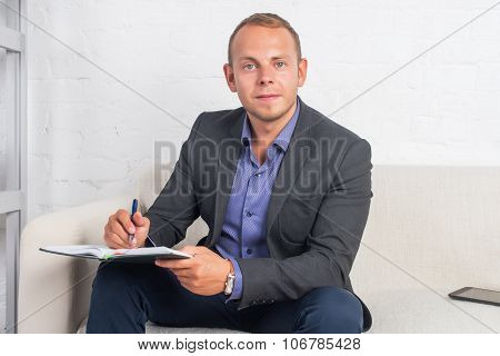 Handsome Businessman Sitting On Couch With Notebook At Home In The Living Room, Looking Camera.