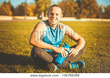 Sporting An Attractive Man Sitting On Grass. Rests In The Stadium And Keeps Shaker Sunny Day.