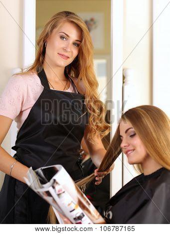 Beautiful Blonde Female Hairdresser Holding Hair Lock