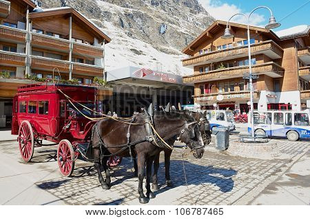 View to the horse carriage waiting for passengers in front of the Zermatt railway station.
