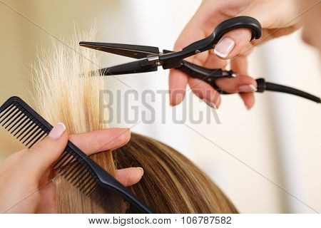 Female hand holding comb and hot thermal scissors cutting tips