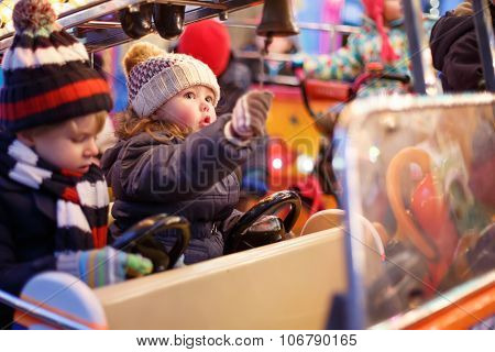 Little Boy And Girl On A Carousel At Christmas Market