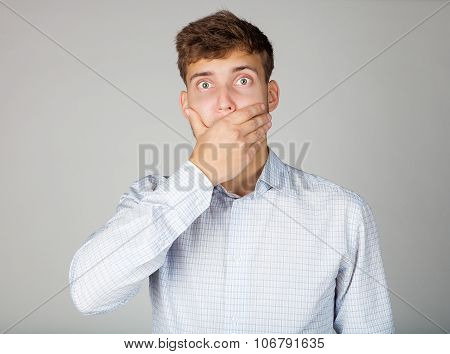 Emotional shocked young business man in white shirt closes his mouth by his hand.