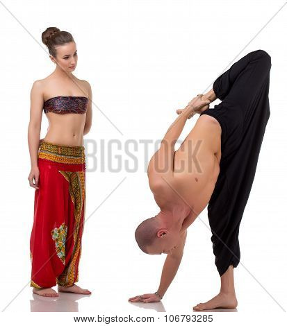 Brunette watches as yoga coach performs asana