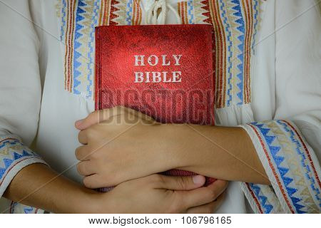 Hand Embracing Red Holy Bible