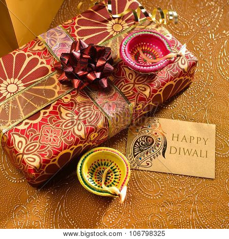 'Happy Diwali' message on a tag along with gift box and lamps. Indian festive background.