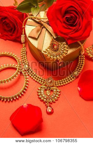 Classic design of an Indian gold necklace and bangles set arranged with heart shape gift box and red rose flowers.