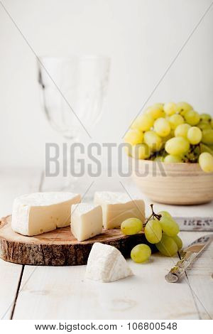 Brie, camembert cheese with fresh grape, wine glass.