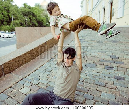 little son with father in city hagging and smiling, casual look outside