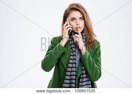 Portrait of a young woman talking on the phone and showing finger over lips isolated on a white background