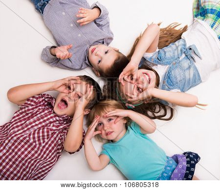 children lying on the floor with hands imitating glasses isolated on white background