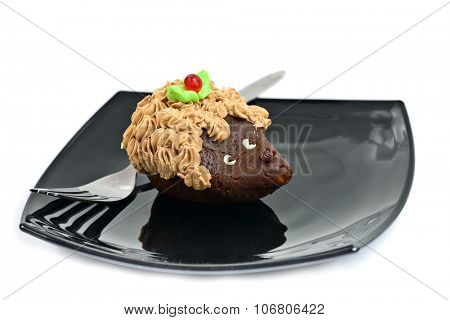 Chocolate cake decorated as hedgehog on black dish isolated