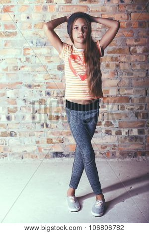 Fashion pre teen girl dressed in sports wear and sneakers posing over brick wall