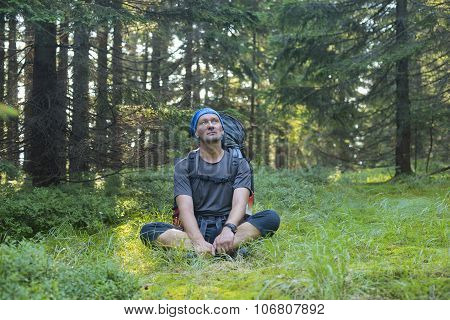 Hiker Resting In A Clearing In The Pine Forest, Thinking About Something Sitting On The Green Grass