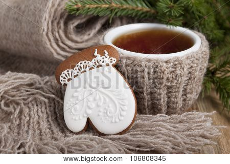 Christmas Cookies In The Form Of Gloves With White Icing And A Cup Of Tea