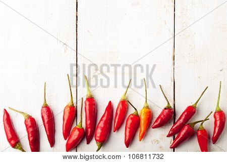 Chili peppers fresh and dry, smoked paprika. White wooden background.