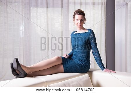 Attractive Woman In Blue Dress Sitting On Couch