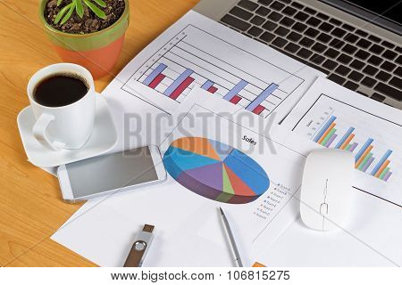 Busy Desktop With Financial Data Print Outs And Technology