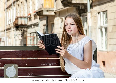 Girl Laying On Bench And Reading Book