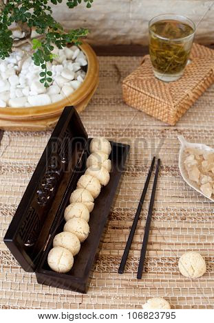 Traditional asian sesame cookies in a wooden box, green tea