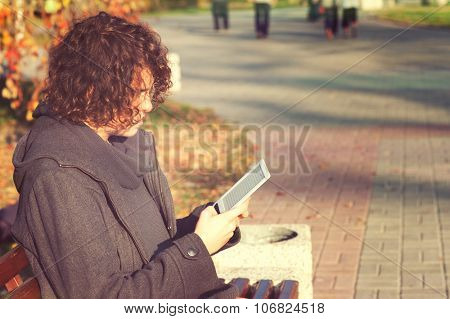 Young stylish man have a leisure sitting in autumn park and reading the electronic book.
