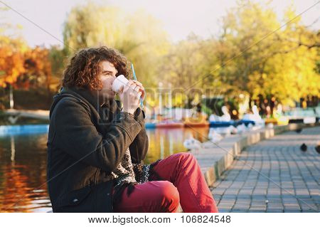 Stylish young man with curly hairstyle sitting on the lakeside in autumn park and  drink some coffee, outdoor relax.