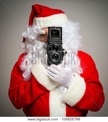 Santa Claus using a vintage camera