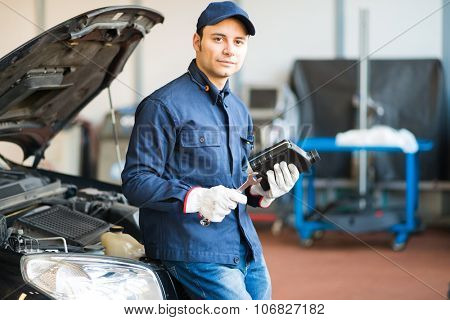 Portrait of an auto mechanic holding a jug of motor oil and a wrench
