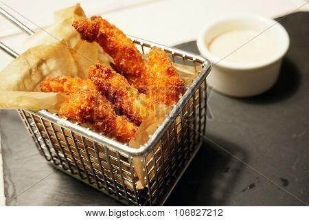 Breaded deep fried chicken served in a metallic fryer basket