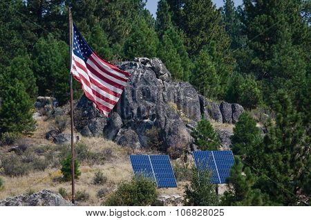 American Flag Standing In The Wilderness Beside Two Solar Panels