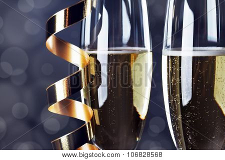 Two champagne glasses and curly ribbons on dark background