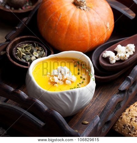 Pumpkin soup with salty popcorn in a white ceramic bowl