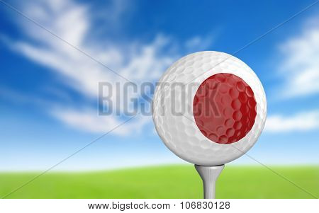 Golf ball with Japan flag colors sitting on a tee