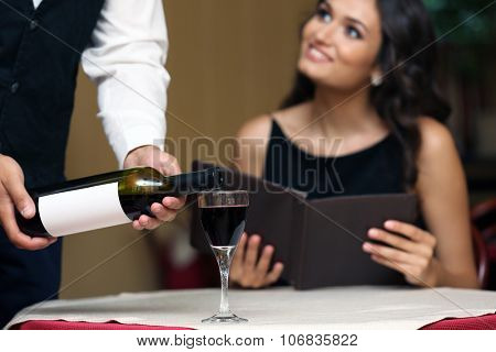 Young pretty lady at the restaurant. Waiter pouring wine in a glass