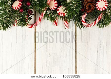 Christmas border of branches and candy canes on white wood