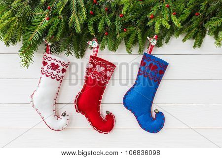 Christmas Background. Christmas Fir Tree With Decoration, Colorful Christmas Socks On White Wooden B