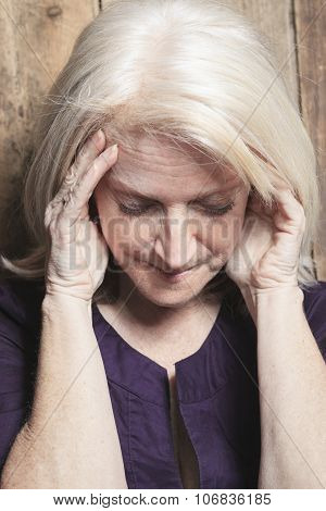 depress senior person with wood background
