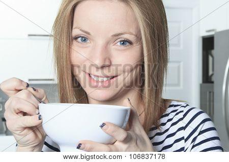 Jolly woman having breakfast at home
