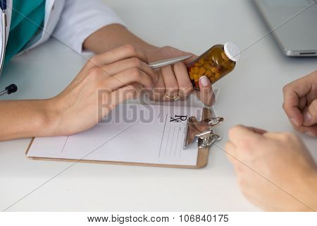 Close-up View Of Female Doctor's Hand Holding Bottle With Pills And Writing Prescription