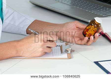 Close-up View Of Female Doctor's Hand Holding Bottle With Pills