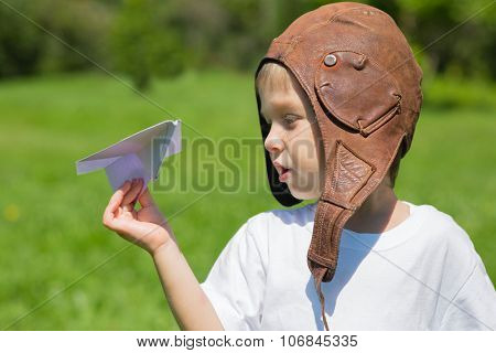 Cute boy in the old helmet pilot playing with paper plane