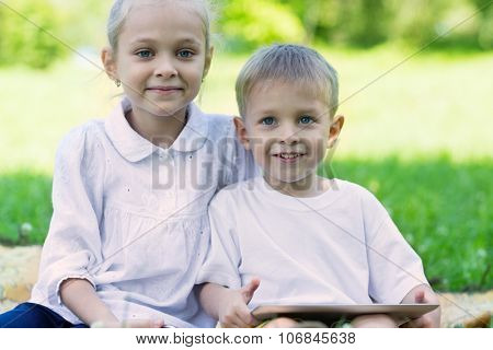 Joyful children use a tablet pc while sitting on the grass in the park. Brother and sister.