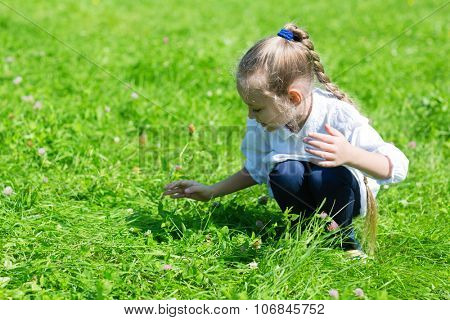Girl catching a grasshopper in the grass in park