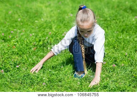Joyful girl with a scythe catches in the grass grasshopper