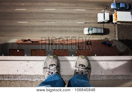 man standing on edge of tall building
