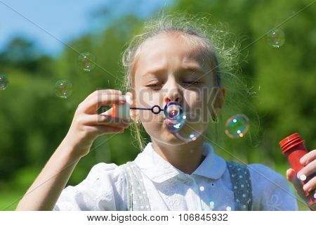 Cute girl blowing soap bubbles on a bright sunny day.