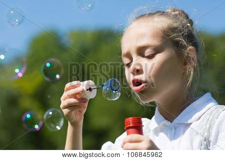 Charming little girl blowing soap bubbles outdoors.