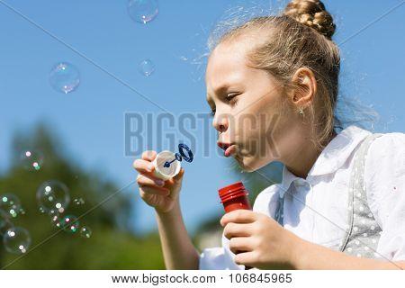 Cute little girl blowing soap bubbles in a park