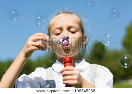 Beautiful girl blowing soap bubbles in a park.