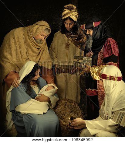 Live Christmas nativity scene reenacted in a medieval barn - the baby is a doll.